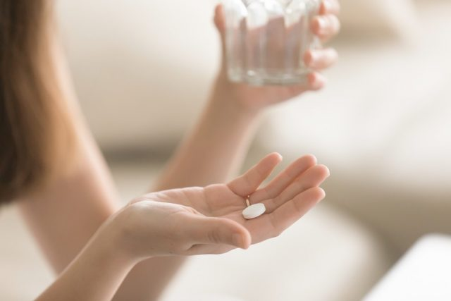Woman takes medicines with glass of water