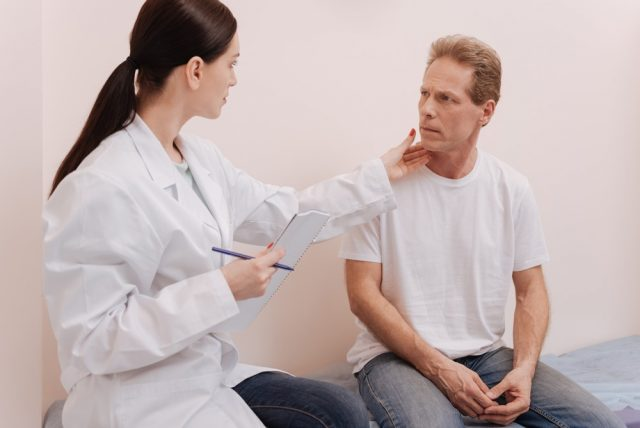 Observant careful doctor looking at mans skin