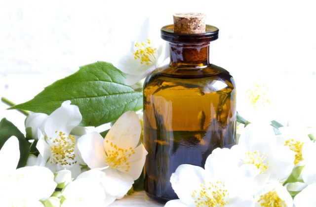 Jasmine aromatherapy oil on white planks with flowers