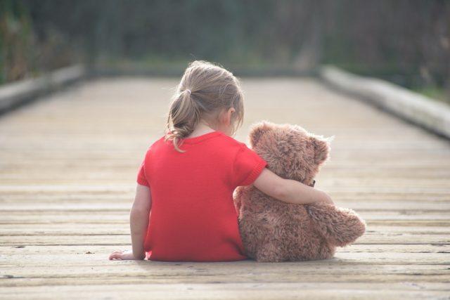 small sad girl with teddybear