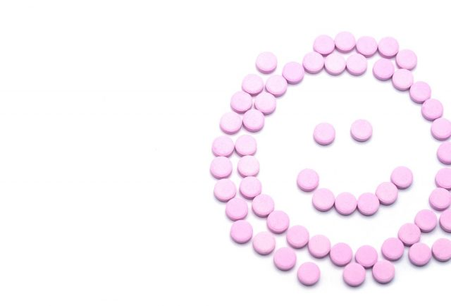 Bloody Discharge - Smile face of pink pills on white background