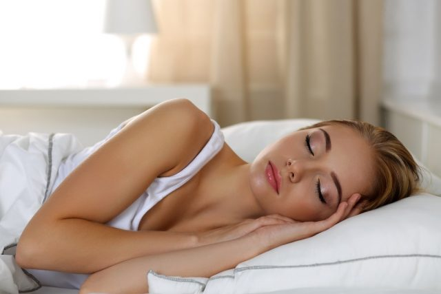 Young beautiful blonde woman portrait lying in bed sleeping late in the morning after hard working day tired