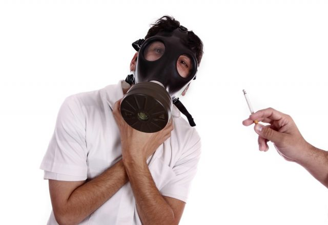 Man wearing a gas mask, trying to avoid pollution