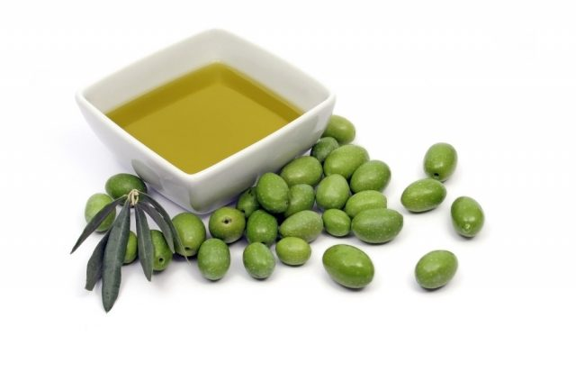 Extra virgin olive oil with fresh green olives