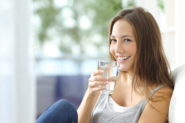Girl drinking water sitting on a couch at home