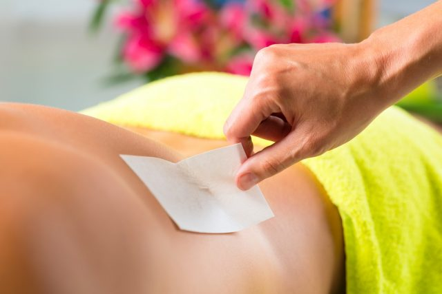 Man in Spa getting back waxed or sugared for hair removal