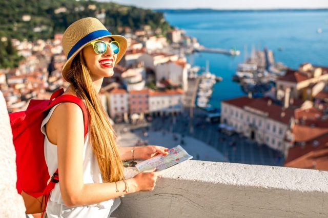 Young female traveler with red backpack and hat enjoying the view from George's tower on Piran old town