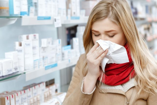 Young woman sneezing in a paper napkin while shopping at the drugstore