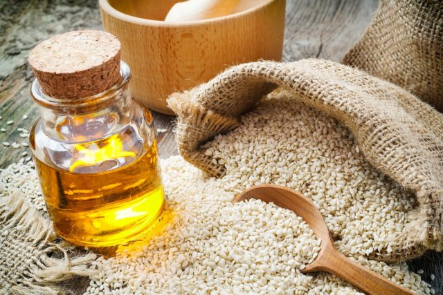 sesame seeds in sack and bottle of sesame oil on wooden rustic table