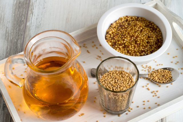 A cup with mustard, a glass with mustard seeds and a jug with mustard oil on a white wooden tray.