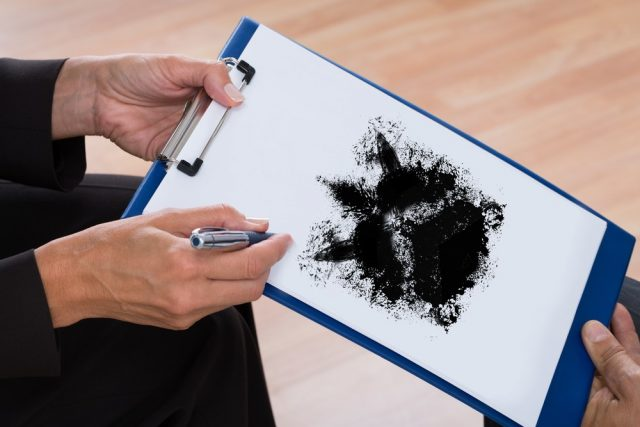 A Psychologist Showing Rorschach Inkblot On Clipboard To Patient
