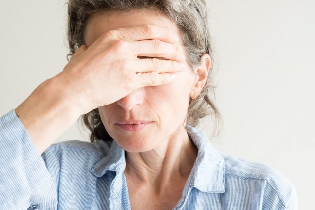 Close up of middle aged woman with hand covering eyes