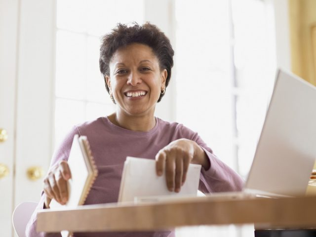 Middle-aged woman smiling for the camera at her desk