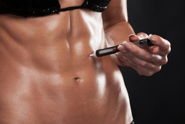 Muscular woman shot on black injecting HGH