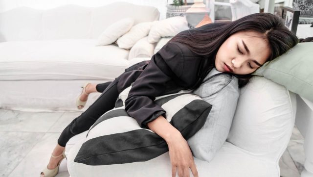Asian business girl lying on a white sofa Fatigue, fatigue, hard work