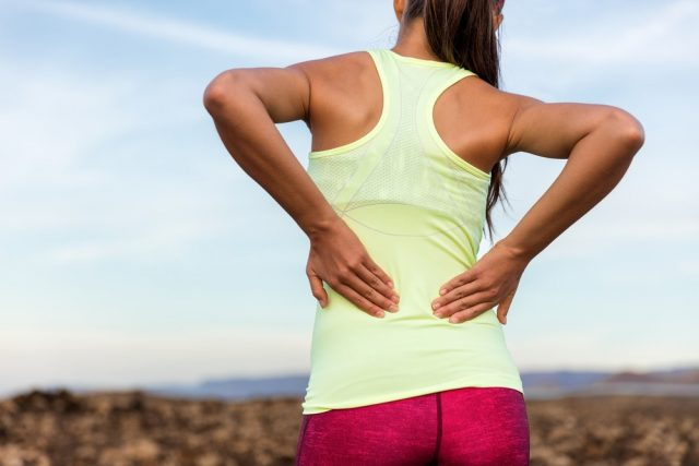 Trail running runner with painful lower back pain injury or strained muscle near the spine