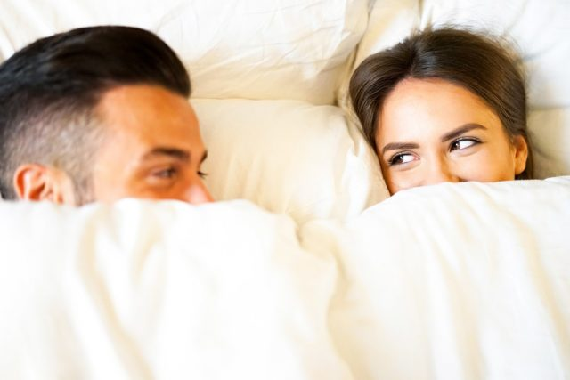 Boyfriend and girlfriend laying in a bed with white sheets - Young and beautiful couple happily looking at each other during bed time