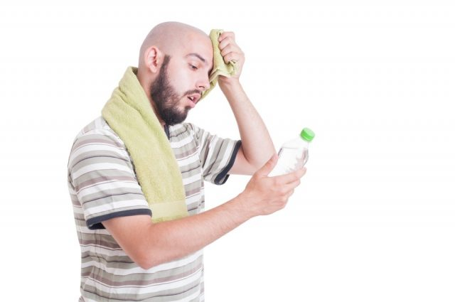 Dehydrated man wiping forehead and holding bottle of water