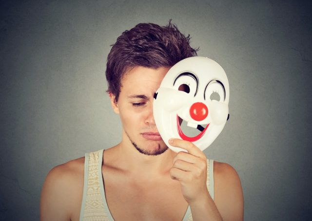 Young sad man taking off clown mask
