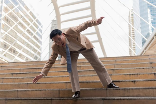 Businessman falling down the steps of staircase